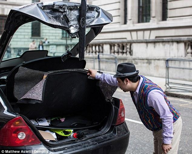 Mr Razi picks over the remains of his mangled car (Picture: Matthew Aslett/Demotix)